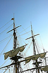 A view of an old sailboat masts against the blue sky.
