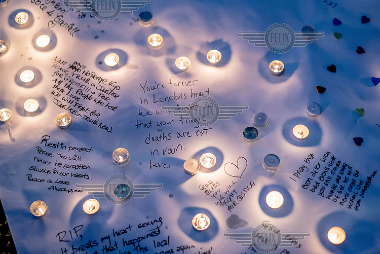 Candles illuminate messages written at a vigil outside the Houses of Parliament to the victims of the Grenfell Tower fire.