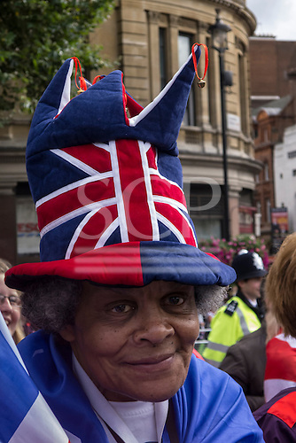 Trafalgar Square, London, Engand. A British supporter with Union Jack hat on her head in the crowds. Olympics celebration.