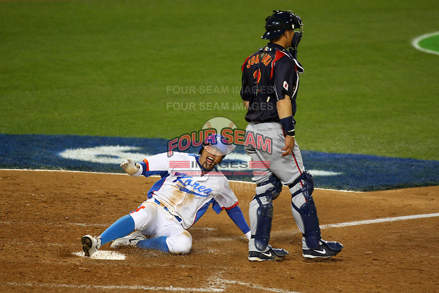 Jong Wook Lee of Korea scores while sliding past Kenji Johjima of Japan at the World Baseball Classic at Dodger Stadium on March 23, 2009 in Los Angeles, California. (Larry Goren/Four Seam Images)