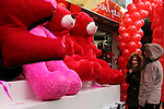 Palestinians walk past a shop selling red teddy bears, red ballons and pillows on Valentine's day in Gaza city on February 14, 2017. Valentine's Day is increasingly popular in the region as people have taken up the custom of giving flowers, cards, chocolates and gifts to sweethearts to celebrate the occasion. Photo by Ashraf Amra