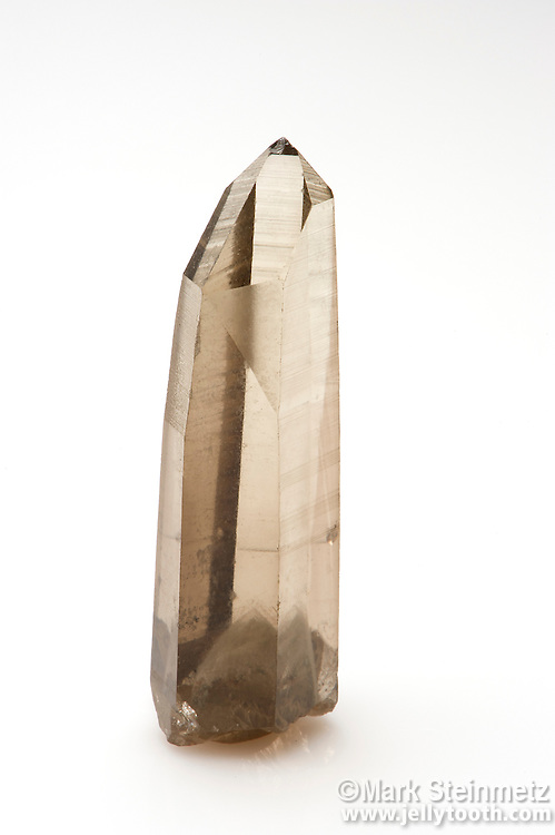 Smoky Quartz with phantom at base, Minas Gerais, Brazil. A phantom is a quartz crystal which grows over an earlier crystal, usually due to a change in growth conditions causing a stoppage or interruption. The  original crystal may have had deposition of fine-grained mineral matter, micro-bubbles, or even rock dust collect on its face during the interruptive period. Such inclusions further highlight the phantom.