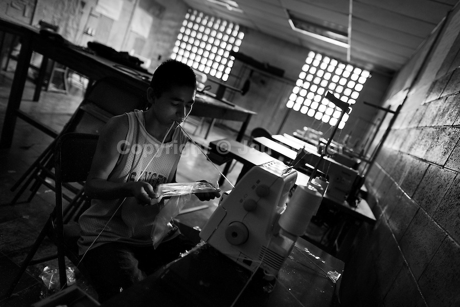 A member of the Mara Salvatrucha gang (MS-13) works on a sewing mashine during the resocialization classes in the prison of Tonacatepeque, El Salvador, 18 May 2011. During the last two decades, Central America has become the deadliest region in the world that is not at war. According to the UN statistics, more people per capita were killed in El Salvador than in Iraq, in recent years. Due to the criminal activities of Mara Salvatrucha (MS-13) and 18th Street Gang (M-18), the two major street gangs in El Salvador, the country has fallen into the spiral of fear, violence and death. Thousands of Mara gang members, both on the streets or in the overcrowded prisons, organize and run extortions, distribution of drugs and kidnappings. Tattooed armed young men, mainly from the poorest neighborhoods, fight unmerciful turf battles with their coevals from the rival gang, balancing between life and death every day. Twenty years after the devastating civil war, a social war has paralyzed the nation of El Salvador.