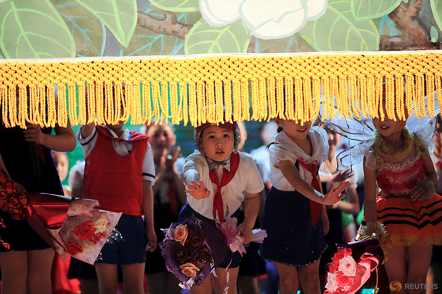 Children wave to spectators as the curtain is brought down at the end of a performance at the Mangyongdae Children's Palace in Pyongyang, North Korea May 5, 2016.  REUTERS/Damir Sagolj
