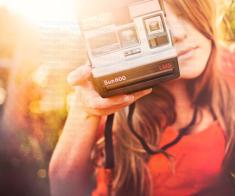 Close up of young woman with blonde hair holding polaroid camera