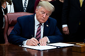 US President Donald J. Trump signs 'H.R. 724, the Preventing Animal Cruelty and Torture Act', in the Oval Office of the White House in Washington, DC, USA, 25 November 2019.<br /> Credit: Michael Reynolds / Pool via CNP