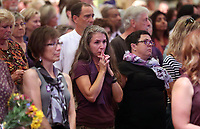 Crowd members react as family members enter during a memorial for Heather Heyer Wed., August 16, 2017, at the Paramount Theater in Charlottesville, Va. Heyer was killed the previous weekend when a vehicle drove into a crowd of counter-protestors after the Unite The Right rally. Photo/Andrew Shurtleff