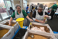 NWA Democrat-Gazette/J.T. WAMPLER Suzane Woolsey (left) and Michelle Sullivan pack macaroni and cheese dinners Wednesday Nov. 6, 2019 at the Donald W. Reynolds Boys & Girls Club of Fayetteville. The United Way of Northwest Arkansas collaborated with Bite Squad, Waitr, and the Northwest Arkansas Food Bank to pack 9,000 meals for Northwest Arkansas residents on Wednesday.<br />