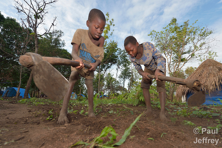 A boy and girl prepare the soil for planting in a camp for more than 5,000 displaced people in Riimenze, in South Sudan's Gbudwe State, what was formerly Western Equatoria. Families here were displaced at the beginning of 2017, as fighting between government soldiers and rebels escalated.<br />