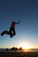 Young girl jumping in air over sunset on sea stacks and sandy beach, Shi Shi Beach, Olympic National Park, Washington Coast, USA
