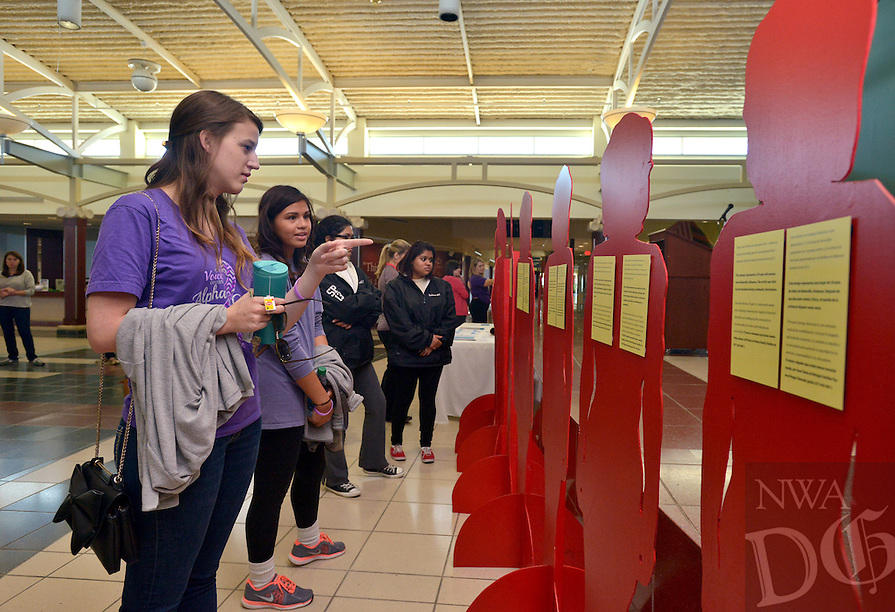 STAFF PHOTO BEN GOFF  @NWABenGoff -- 10/04/14 Kristen Jenson, left, and Alyssa Ison, read the stories on the 'The 'silent witnesses' silhouettes representing the 18 victims of domestic partner or family homicide in Arkansas in 2013, while participating in the Peace at Home Family Shelter's Domestic Violence Awareness Month Kickoff event with Alpha Chi Omega sorority from the University of Arkansas at the Jones Center in Springdale on Saturday October 4, 2015.