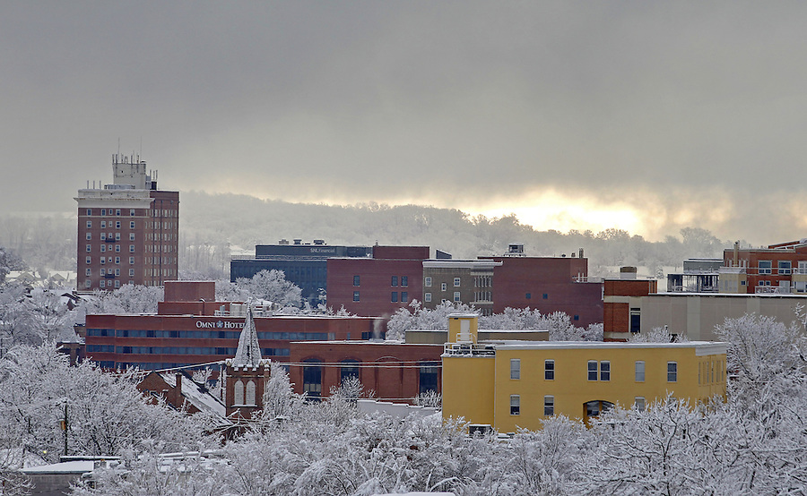 The clouds begin to break over a snow covered Downtown Charlottesville, VA. skyline. Photo/Andrew Shurtleff