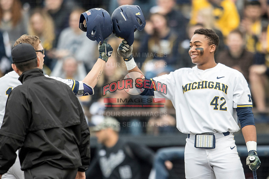 Michigan Wolverines outfielder Jordan Nwogu (42) greets teammate Dominic Clementi (13) at the plate against the Maryland Terrapins on April 13, 2018 in a Big Ten NCAA baseball game at Ray Fisher Stadium in Ann Arbor, Michigan. Michigan defeated Maryland 10-4. (Andrew Woolley/Four Seam Images)
