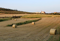 Stock image - Hay rolls arrangement on a slope farm land in Cyprus with an monastery in the background.