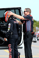 Apr 10, 2015; Las Vegas, NV, USA; A crew member helps NHRA top fuel driver Steve Torrence donning his safety gear during qualifying for the Summitracing.com Nationals at The Strip at Las Vegas Motor Speedway. Mandatory Credit: Mark J. Rebilas-