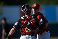 Hickory Crawdads relief pitcher Nick Snyder (25) hugs catcher Matt Whatley (19) after getting the final out in the game against the Greensboro Grasshoppers at L.P. Frans Stadium on May 26, 2019 in Hickory, North Carolina. The Crawdads defeated the Grasshoppers 10-8. (Brian Westerholt/Four Seam Images)