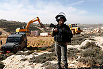 Security forces stand guard as Israeli bulldozers raze agricultural land in Wad al-Seman near the West Bank city of Hebron, January 23, 2019. Local sources confirmed that the bulldozers of the occupation swept about 15 dunums of land, and retaining walls in the area south of Hebron. Photo by Wisam Hashlamoun