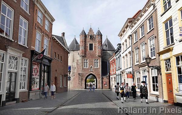 Nederland - Bergen op Zoom -  16september 2018. De Gevangenpoort (ook Lievevrouwepoort ) in Bergen op Zoom is het oudste monument van de stad. De poort dateert uit de 14e eeuw en is één van de overgebleven voorbeelden van stadspoorten zoals die in de middeleeuwen in Nederlandse steden te vinden waren. Het is de enige stadspoort overgebleven in Bergen op Zoom. Rechts lopen leden van een gilde op weg naar de opstelling voor de Brabant Stoet. Foto Berlinda van Dam / Hollandse Hoogte