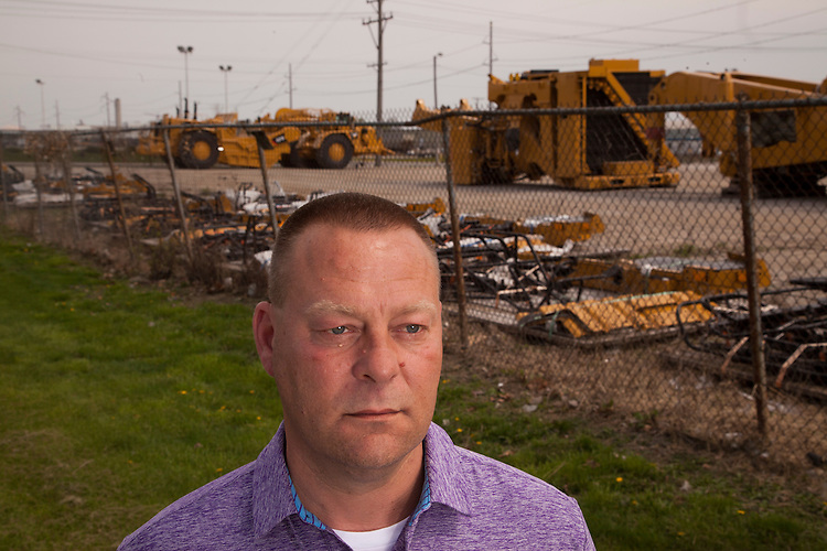 Denny Ryder was laid off from Caterpillar in late 2013, and left Decatur, his hometown, to work for a Caterpillar contractor in North Carolina. Ryder is shown during a return visit in front of Keen Transport across from the Caterpillar plant. Longtime industrial city Decatur, Ill., had the country&rsquo;s greatest unemployment rate reduction. But people leaving the workforce &ndash; moving away, retiring, no longer looking for jobs -- may be the cause, rather than economic expansion. <br /> CREDIT: Kristen Schmid for the Wall Street Journal<br /> RUSTBELT