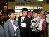 Note: All names correct.<br /> STAFF PHOTO FLIP PUTTHOFF <br /> Manas Chithirala, from left, Teju Koppula and Abhi Madhavan show each other their immigration papers on Wednesday Dec. 17 2014 during the Ellis Island re-enactment at Ruth Barker Middle School in Bentonville.