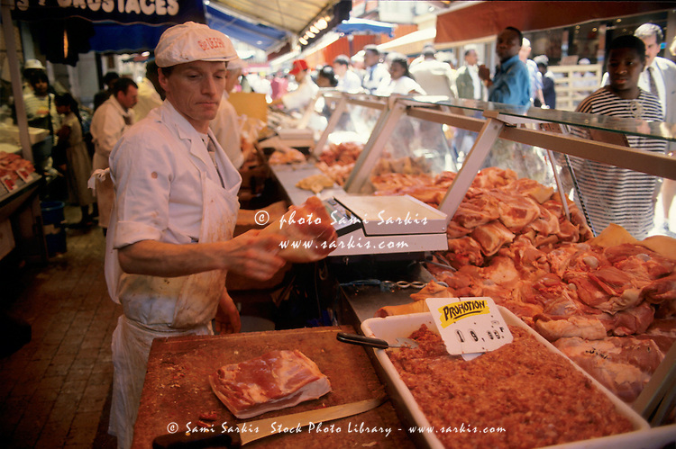 Man working in a butchery at the Marché Barbès in Goutte d'Or, 18th arrondissement, Paris, France.
