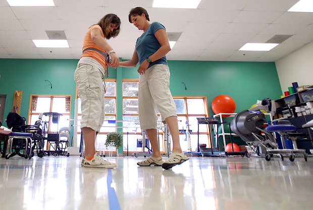 Elizabeth works on her balance with physical therapist Shannon Wieland at On With Life, a brain injury rehabilitation center in Ankeny.  She has made swift strides in recovering from her severe brain injury.
