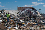A worker sprays water on demolition debris to keep down dust as as wrecking crews remove a large portion of Westerville Square Shopping Center to make way for the construction of a new WalMart store in the Columbus suburb. The store will approximately 108,000-square-feet, about half the  size of a traditional WalMart super store..