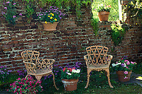 Old brick wall of outbuilding converted into patio and garden next to house, with touches of color and chairs