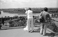 Belgrado, due signore di mezza età scrutano la città con il cannocchiale panoramico dalla fortezza nel Parco Kalemegdan presso la confluenza del fiume Sava nel Danubio --- Belgrade, two middle-aged ladies looking through the panoramic telescope at the fortress in Kalemegdan Park, near the confluence of the Sava river and the Danube