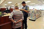 A Clinton police officer checks Amanda's purse for illegal prescriptions as she waits already in handcuffs. The officer did find other illegal drugs in her purse resulting in a felony possession of a controlled substance charge. Later, Amadna admitted that she stole prescription from doctor`s office a couple days before@s visit for her backpain.