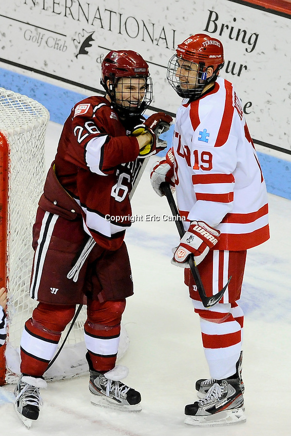 Harvard Crimson forward Luke Greiner (26) and Boston University Terriers forward Matt Nieto (19) during the Harvard University at Boston University NCAA hockey match held at the Agganis Arena in Boston Massachusetts.   Eric Canha/CSM