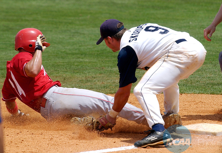04 JUNE 2005:  Alexy Hernandez (14) of Florida Southern slides safely between the feet of North Florida's Jon Skorupski (9) after hitting a triple in the seventh inning during the Division II Men's Baseball Championship held at Riverwalk Stadium in Montgomery, AL.  Florida Southern defeated North Florida 12-9 for the national title.  David Bundy/NCAA Photos