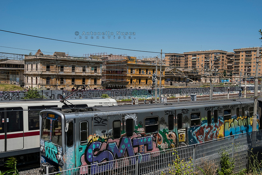 Rome, Italy, June 21, 2017. Trains and buildings. Treni della metropolitana in transito tra i palazzi del quartiere Ostiense.<br /> Ad un anno dalla elezione a sindaco di Roma di Virginia Raggi, la condizione di degrado non accenna a migliorare.<br /> One year after the election as mayor of the candidate of M5S party, Rome is worsening day by day.