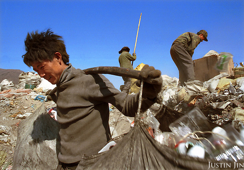Zhang, working thousands of miles away from home, carries trash he fetched at a garbage mount on the outskirts of Beijing. ..The scavenger is among some 50 people from a farming village in the southwestern province of Sichuan, who were driven to the relatively rich Chinese capital by bleak job opportunities at home...Here the workers pick, sort and sell anything from beer bottles to rotting bread seven days a week for a monthly income of about 300 yuan, which compares handsomely with an annual household income of about 1,000 yuan at their village. ..Picture taken March 1999.Copyright Justin Jin