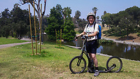 "Holland poses with his Yedoo Dragstr aluminum-frame, 20"" wheel kick scooter in Hollenbeck Park during the 2017 (17th annual) Los Angeles River Ride.  Holland's customized higher-than-normal handlebars and the water bottle attachment can be seen.  Palm and other trees can be seen around the lake in the background."