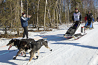 Peter Kaiser and team run past spectators on the bike/ski trail during the Anchorage ceremonial start during the 2014 Iditarod race.<br /> Photo by Britt Coon/IditarodPhotos.com