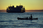Washington State ferry on Puget Sound heading toward Edmonds, Washington with man in canoe and crab pods silhouetted at sunset, Edmonds, Washington State USA