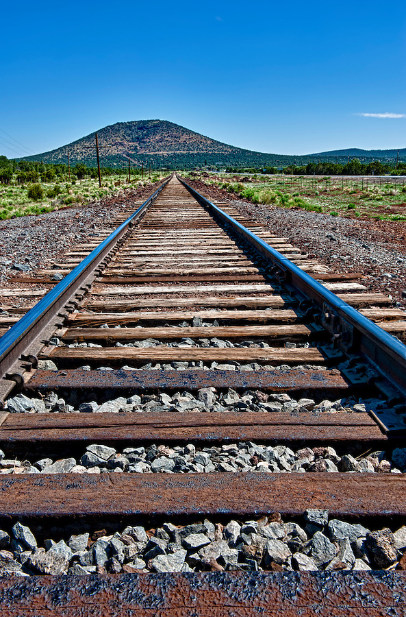 Railway tracks in the countryside, leading to a mountain.