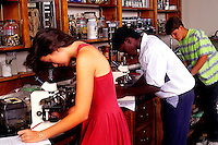 Mixed ethnic students hispanic and black in high school biology class experiments with microscope in schoo