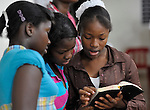 Young women read the Bible together duriing worship in an evangelical church in La Hoya, a small rural town near Barahona in the southwest of the Dominican Republic. This service brings together Dominicans and Haitian-Dominicans from a nearby batey in an unusual demonstration of unity in a land where discrimination against Dominicans of Haitian ancestry is growing.