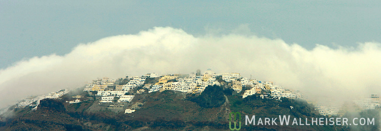 A rare rain storm gathers over the island of Santorini, Greece.