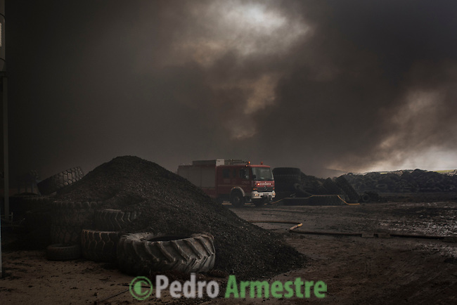 Clouds of dark smoke cover the sky as a fire truck drives among piles of tyres in an uncontrolled dump near the town of Sesena, after a fire broke out early on May 13, 2016. A huge waste ground near Madrid where millions of tyres have been dumped was on fire today, releasing a thick black cloud of toxic fumes that officials worry could harm residents nearby.  © Pedro ARMESTRE