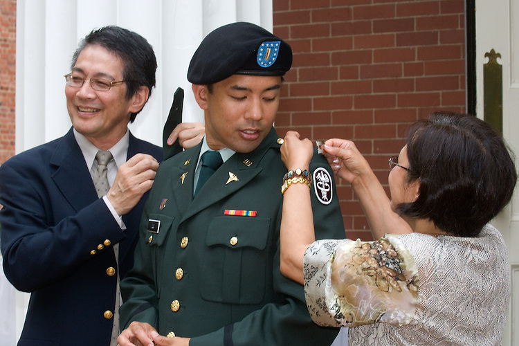 Myro Lu, D. O., receives his re-commissioning from his parents following his graduation June 7 from the Ohio University College of Osteopathic Medicine.