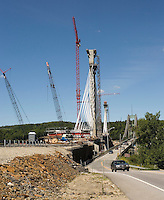 BRIDGE CONSTRUCTION<br /> Penobscot Narrows Bridge, A Cable Stayed Bridge<br /> Cars driving on the older Waldo-Hancock Bridge, a suspension bridge, next to construction site. A cable-stayed bridge is a bridge that consists of one or more columns, with cables supporting the bridge deck.