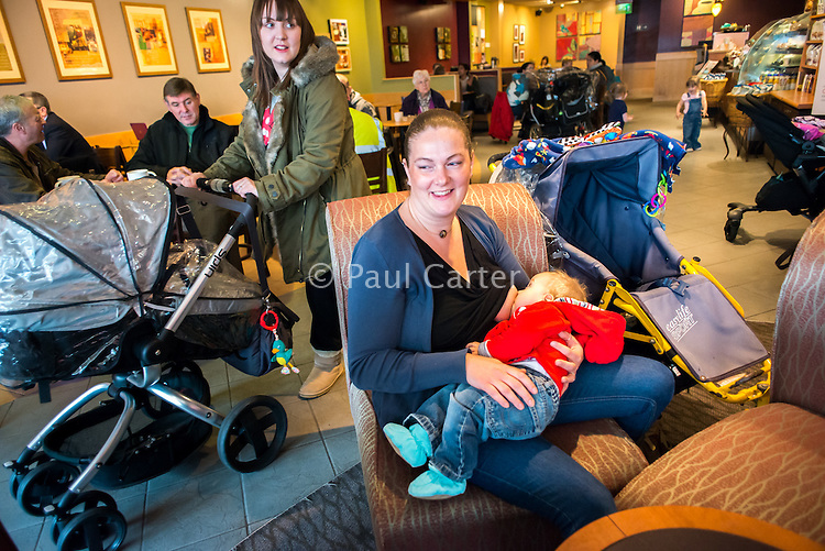 A mother breastfeeding her baby in a coffee shop while another mother passes in the background pushing a pram.<br /> <br /> Image from the &quot;We Do It In Public&quot; documentary photography project collection: <br />  www.breastfeedinginpublic.co.uk<br /> <br /> Dorset, England, UK<br /> 17/04/2013