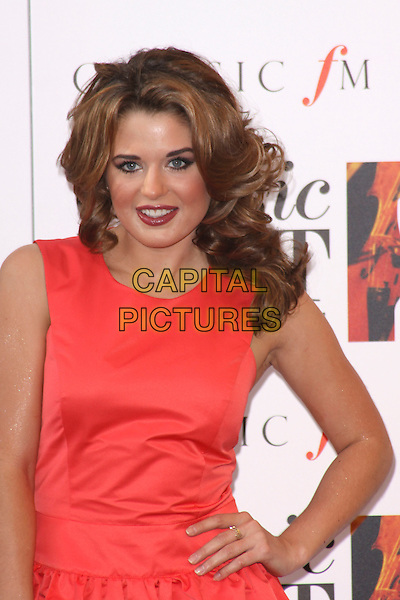 COURTENAY HAMILTON (Miss wales 2010).Arriving to the Classical Brit Awards 2011 at the Royal Albert Hall, London, England, UK, 12th May 2011..arrivals brits half length red dress sleeveless  make-up lipstick gold cuff  hand on hip .CAP/AH.©Adam Houghton/Capital Pictures.