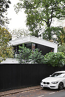 The exterior of the modern eco house as seen above a garden fence.