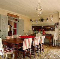 Hunting trophies and a painting of the African landscape adorn the walls in this outside dining room