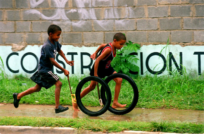 Kids run together racing their tires guided with stick as their form of outdoor fun and exercise.