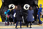 Passersby look at a big cat face on display in Shibuya station on April 5, 2015, Tokyo, Japan. The Japanese courier service Yamato Transport Co., LTD. is using this innovative display to promote its two new services for small packages from April 1st. (Photo by Rodrigo Reyes Marin/AFLO)